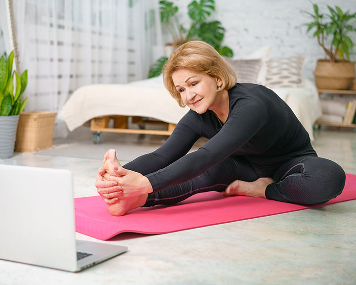 Woman doing yoga in her living room in front of a laptop